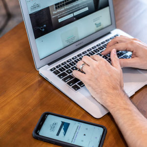 man typing with private practice elevation website on computer